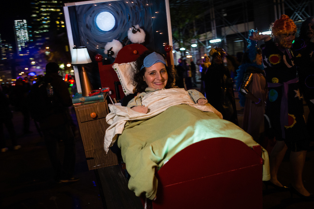 """New York, NY - 31 October 2016. A woman costumed as if in bed, with a night stand, headboard, and background with a painting reminiscent of Van Gogh's """"Starry Night."""""""