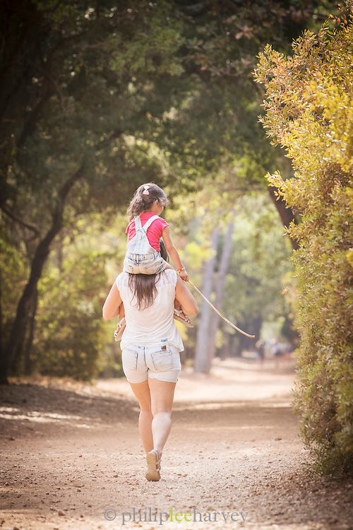 Woman giving small girl piggyback while on walk along forest path on sunny day