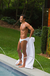 man taking off his robe by a swimming pool