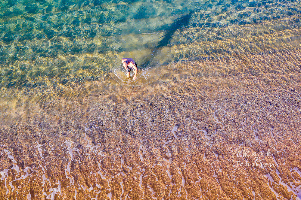 Aerial view of a man exiting the ocean after swimming off of Shelly Beach, Caloundra, Sunshine Coast, Queensland, Australia