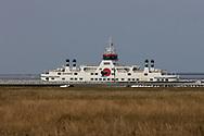 Veerboot Sier van Wagenborg Passagiersdiensten vaart langzaam door de ondiepe vaargeul vanaf Ameland naar de veerdam bij Holwerd. Vanwege de ijsgang in de Waddenzee zijn de sneldiensten naar en van de eilanden komen te vervallen.