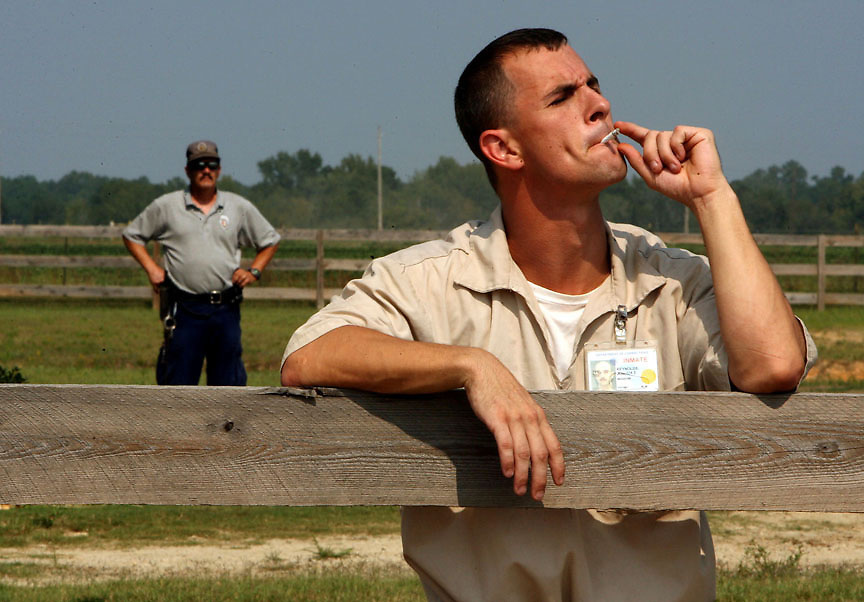 Wateree Correctional Institution officer, Eddie Stock, supervises inmate Joshua Reynolds, 27, while he takes a smoke break.Photography by Chris Aluka Berry/ ALUKAStorytelling Photography.com)