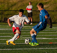 Laconia's James Salta and Interlakes Tommy DeTolla battle for the ball during Tuesday nights NHIAA Division III Soccer.  (Karen Bobotas/for the Laconia Daily Sun)