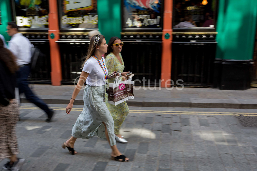 Lunchtime women City workers carry their identical takeaway food packages along Watling Street the former Roman thoroughfare in the City of London, the capitals financial district aka the Square Mile, on 22nd August 2019, in London, England.