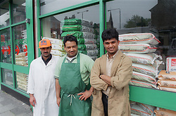 Staff of the Mogal Superstore standing together outside shop on Radford Road; in Hyson Green; Nottingham,