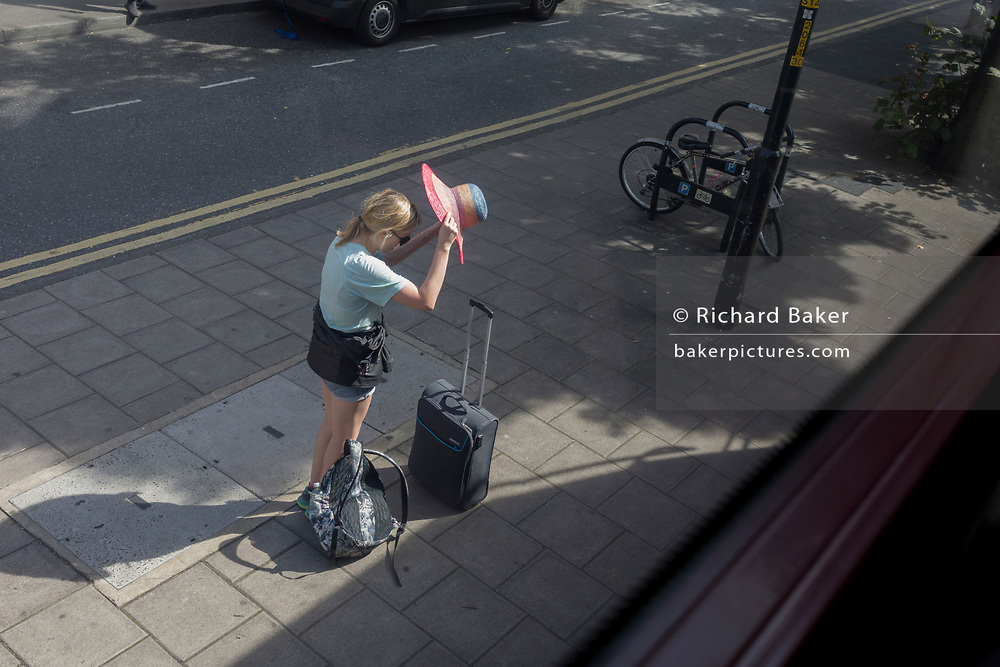 One of a sequence of four images of a young woman placing a floppy wide-brimmed sunhat on her head at a south London bus stop, on 29th August 2019, in  London, England.