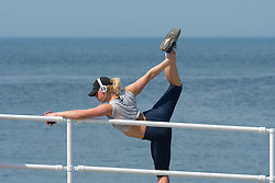© Licensed to London News Pictures. 12/05/2016. Aberystwyth, Wales, UK. A young woman does her stretching exercises at the seaside in  Aberystwyth on the last day of warm weather in the current mini-heatwave. The temperatures are set to fall over the coming days, with bright but colder conditions prevailing over the country .  Photo credit: Keith Morris/LNP