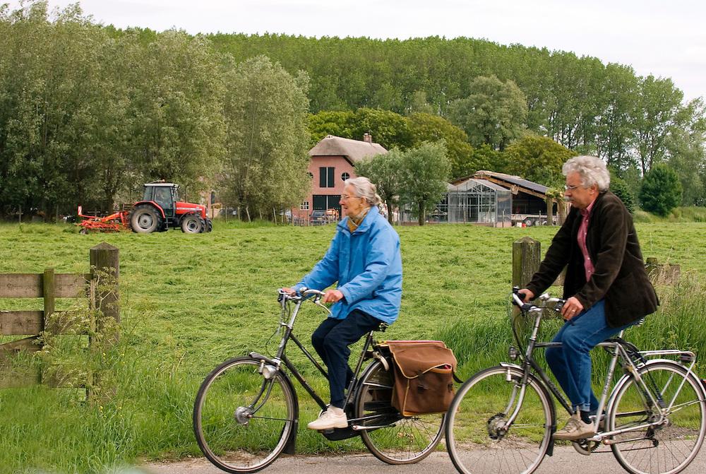 Nederland,   de Meern, 4 juni   2006..Landbouw en recreatiegebied rond kasteel Haarzuilen..Vroeger puur agrarisch gebied, nu, door de nabijheid van grote steden, neemt de toeristische druk enorm toe. Boeren verdwijnen, toerisme komt..Ouderen, oudere mensen, bejaarden maken een fietstochtje langs weilanden waar een boer aan het gras keren is..Fietsen, fietsers, fiets, fietstoerisme, fietspad, recreatie...Foto (c) Michiel Wijnbergh...cycling, bicycle, recreation, turism, .old people cycling