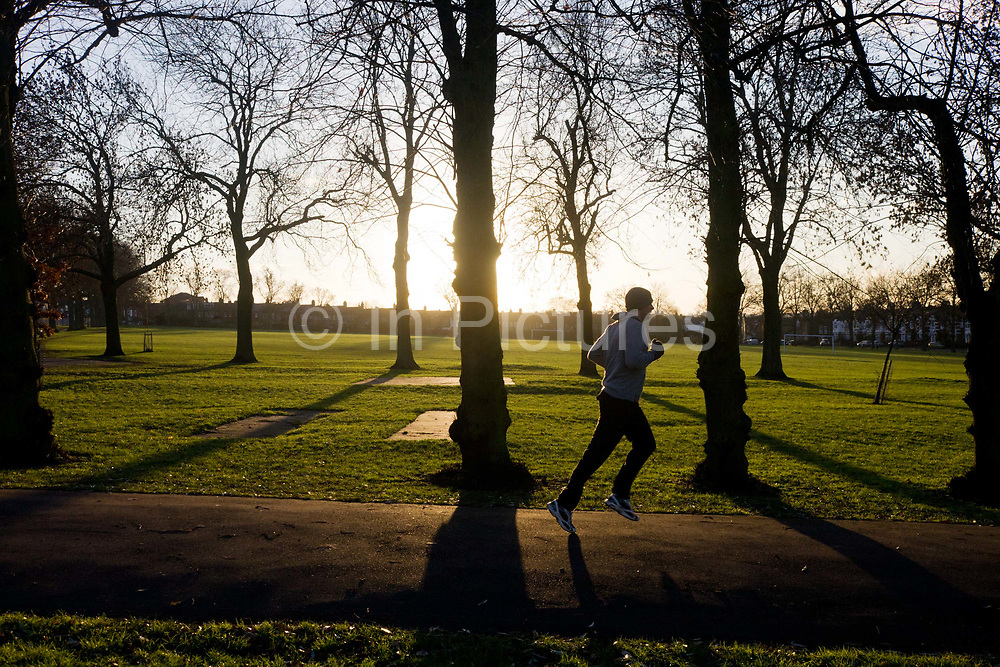 A male jogger exercises in a wide landscape of late winter light of south London's Ruskin Park. Jogging downhill along a path between silhouetted trees, the man is seen against the strong, low sun in the west. Surrounding the open space are the Victorian homes of Londoners who look out onto this protected location, owned by Lambeth and Southwark councils. It is early December and the winter has yet to grip the capital - the first snows being a short time away - and the mild weather attracts this male to a quiet moment during the day.