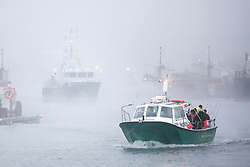 © Licensed to London News Pictures. 01/10/2015. Whitby, UK. Picture shows fishing boats leaving Whitby harbour in this mornings fog. The fishing town of Whitby awoke to a thick covering of fog but the weather is due to brighten up later today. Photo credit: Andrew McCaren/LNP