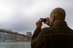 Man photographing The Brooklyn Bridge With A Phone Camera