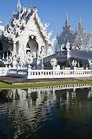 """Wat Rong Khun is unique in Thailand, as its ubosot or consecrated assembly hall is designed in white color and white glass. White color stands for Lord Buddha's purity; the white glass stands for Lord Buddha's wisdom that """"shines brightly all over the Earth and the Universe.""""  The creation of Chalermchai Kositpipat - who volunteered to design the temple at his own expense as an offering to Lord Buddha - he later altered the plan in such a way that Wat Rong Khun developed into a prominent site attracting both Thai and foreign visitors."""