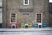 Red yellow and blue chairs outside a cafe in Wapping, London, UK. Colourful addition to this Victorian Street.