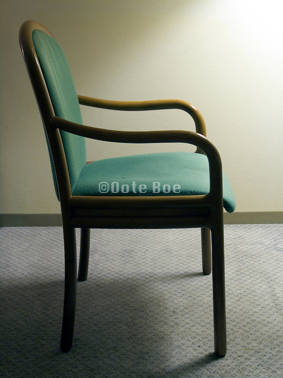 side view of an empty chair in a motel room