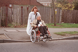 Carer pushing man with disability in manual wheelchair across road,