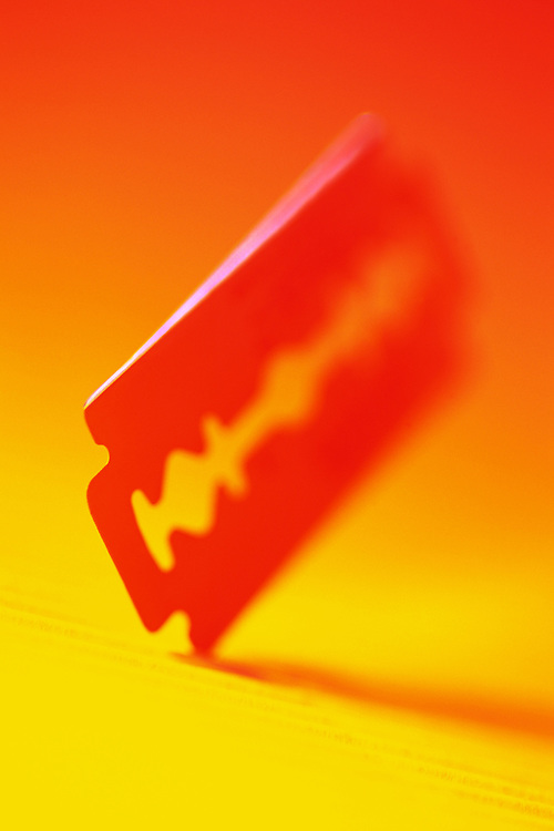Brightly colored, razor blade stuck and standing up on yellow table