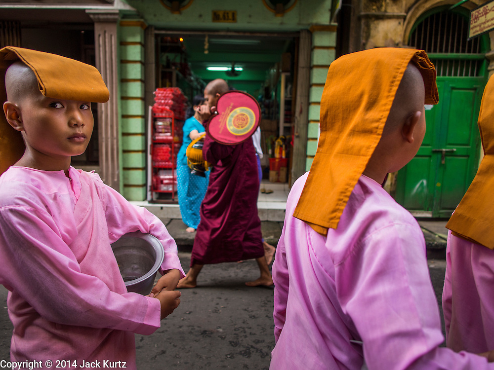 "03 NOVEMBER 2014 - YANGON, MYANMAR:  Buddhists ""nuns"" on their morning alms rounds in Yangon, Myanmar. Nuns in the western sense don't exist in Myanmar, the girls are not actually ordained as nuns. Most come from very poor families. In some cases, their families couldn't afford to keep the girls so they were sent to live in religious environment. The girls will never be ordained as either monks or nuns, but they live a spiritual life, studying Buddhist theology and meditation and doing good deeds. In turn they are supported by their communities.    PHOTO BY JACK KURTZ"