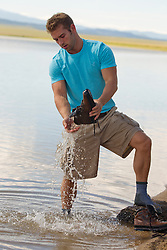 man pouring water from his boot after a walk in a lake