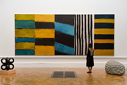 "© Licensed to London News Pictures. 08/06/2017. London, UK. A visitor views ""Full House"" by Sean Scully RA, which is hung between two sculptures (L to R) ""Volute IV"" by Paul de Monchaux and ""Warp and Woof"" by Peter Randall-Page RA. Preview of the Summer Exhibition 2017 at the Royal Academy of Arts in Piccadilly.  Co-ordinated by Royal Academician Eileen Cooper, the 249th Summer Exhibition is the world's largest open submission exhibition with around 1,100 works on display by high profile and up and coming artists.<br />  Photo credit : Stephen Chung/LNP"