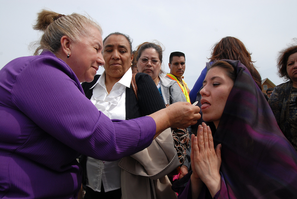 After portraying a biblical figure in a traditional Good Friday Living Way of the Cross procession, Elizabeth Rivera accepts communion during an outdoor mass attended by several thousand parishioners and Archbishop Francis Cardinal George at Most Blessed Trinity Parish in Waukegan.