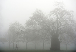 © Licensed to London News Pictures. 01/04/2014. Hammersmith, UK . A man walks across the shrouded fields. A foggy morning in Ravenscourt Park in Hammersmith West London today April 1st 2014. Photo credit : Stephen Simpson/LNP