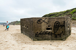 Still waiting for the enemy that never came and sprayed with graffiti both inside and out, a lozenge shaped pillbox half filled with sand sits on the beach having fallen from the cliff due to coastal erosion. The four frontal firing slits still facing in roughly the direction they would have done when originally built during the early 1940's<br /> <br />  29 May 2016<br />  Copyright Paul David Drabble<br />  www.pauldaviddrabble.photoshelter.com