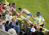 Punters loose their inhibitions after the last race as this reveller receives a pinch on the bottom from a policeman after retreating back to the madding crowd during Victoria Derby Day at Flemington Racecourse in 2002. (Copyright Michael Dodge/Herald Sun)