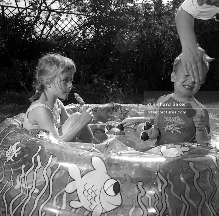 Sitting in cool water of a paddling pool, a 7 year-old girl enjoys an ice lolly while her younger brother winces as he has suncream wiped across his face.