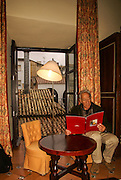Mature man in his hotel room after a day of siteseeing. Photographed in Ubeda, Spain. Model release available