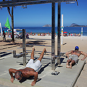 Fitness enthusiasts works out at fitness workstation on the edge of Ipanema Beach, Rio de Janeiro, Brazil. 4th July 2010. Photo Tim Clayton..The beaches of Rio de Janeiro, provide the ultimate playground for locals and tourists alike. Beach activity is in abundance as beach volley ball, football and a hybrid of the two, foot volley, are played day and night along the length and breadth of Rio's beaches. .Volleyball nets and football posts stretch along the cities coastline and are a hive of activity particularly at it's most famous beaches Copacabana and Ipanema. .The warm waters of the Atlantic Ocean provide the ideal conditions for a variety of water sports. Walkways along the edge of the beaches along with exercise stations and cycleways encourage sporting activity, even an outdoor gym is available at the Parque Do Arpoador overlooking the ocean. .On Sunday's the main roads along the beaches of Copacabana, Leblon and Ipanema are closed to traffic bringing out thousands of people of all ages to walk, run, jog, ride, skateboard and cycle more than 10 km of beachside roadway. .This sports mad city is about to become a worldwide sporting focus as they play host to the world's biggest sporting events with Brazil hosting the next Fifa World Cup in 2014 and Rio de Janeiro hosting the Olympic Games in 2016...