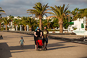 A couple in face masks walk along the promenade in Playa Matagorda, Lanzarote, Spain on 22nd November 2020. Beaches and resorts across the island are nearly deserted since tourism plummeted due to Covid restrictions elsewhere in Europe. Although the Canary Islands have been relatively unscathed by the virus, with 155 lives lost from 2.1 million residents, the region is heavily dependent on tourism and locals are hoping that numbers recover as lockdown measures ease and vaccines potentially reduce the numbers of infections.