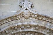 Carved stone face on doorway arch of village church,  Cuacos de Yuste, La Vera, Extremadura, Spain