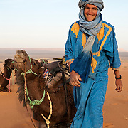 Moroccan man and camels in the Sahara desert near Erfoud, Morocco