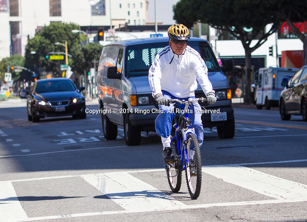 A man rides his bike at downtown Los Angeles Tuesday, September 16, 2014. Starting today, drivers in California must give bikes a buffer zone of at least three feet while passing or face a fine of $35, according to a new law intended to better protect cyclists from aggressive drivers.(Photo by Ringo Chiu/PHOTOFORMULA.com)
