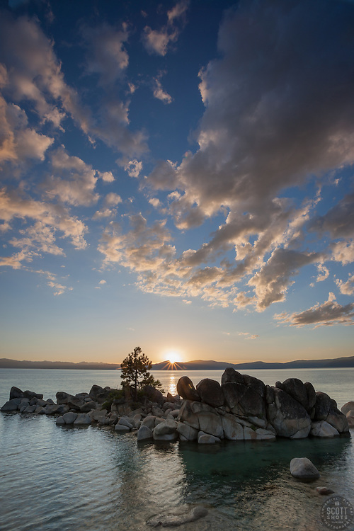 """""""Sunset at Whale Beach, Tahoe 1"""" - Photograph of the sun setting above boulders and a tree at Whale Beach, Lake Tahoe."""