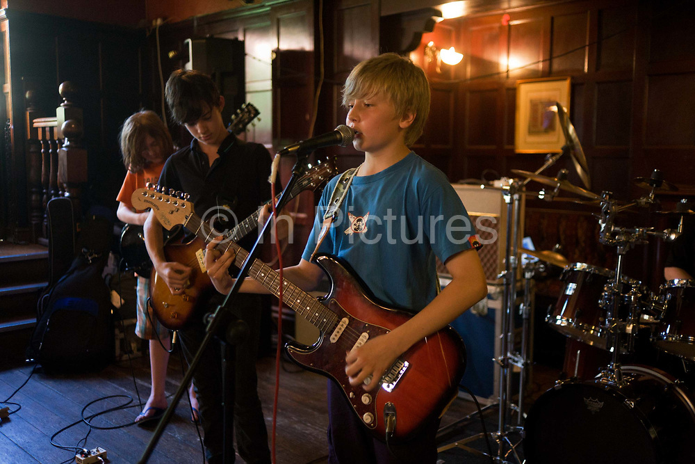 Schoolboys perform rock and roll song together as a band in a south London pub. With the lead singer standing confidently at the microphone and the others concentrating hard on their chords, they perform during a rehearsal for a local music showcase. The young lad is about thirteen (13) years of age and unusually, he plays his electric Fender Squier Stratocaster left-handed guitar with ease. Over his left shoulder we can see part of a drum kit and the amplifiers in the background too. The venue is a pub in south London where the children play will be playing for proud parents and friends and they practice over two weeks, the songs allocated to them by their guitar teacher.