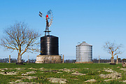 Windmill, water tank and grain silo in farm paddock in rural country Victoria, Australia. <br /> <br /> Editions:- Open Edition Print / Stock Image