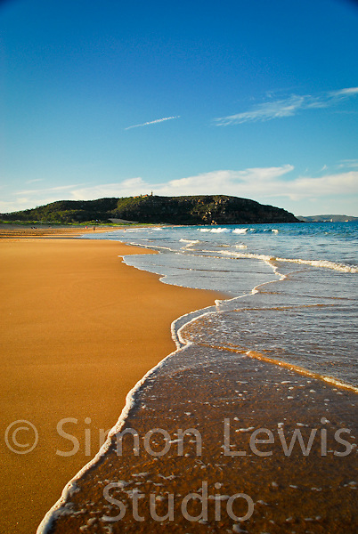 Beautiful, wide open beach in Sydney Australia, deserted at sunset with small waves lapping the sand and a hill in the background