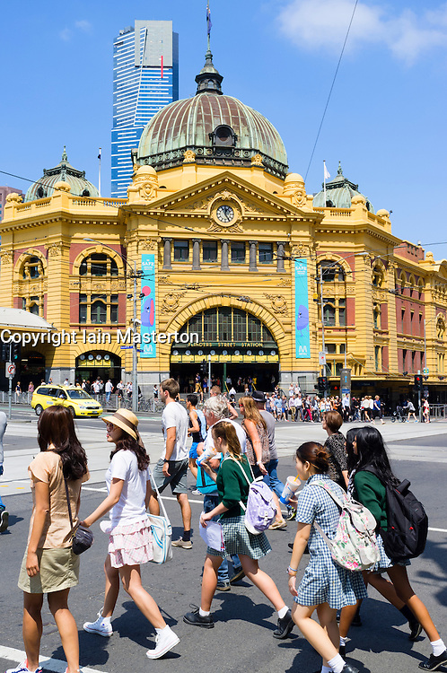 Pedestrians crossing street in front of historic Flinders Railway Station in central Melbourne Australia