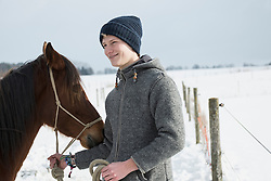 Young man with horse standing in snowy landscape, Bavaria, Germany