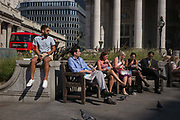 City workers in front of the Victorian columns of the Royal Exchange and the Bank of England, enjoy sunshine in Bank Triangle during an unusual autumn heatwave on 13th September 2016, in the City of London, England.