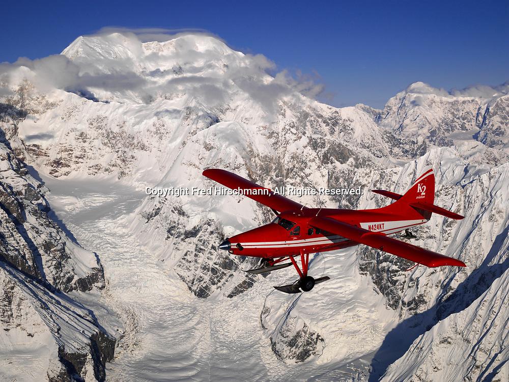 K2 Aviation's Turbo Otter on wheel skis flying past 17,400-foot Mount Foraker in Denali National Park, Alaska.