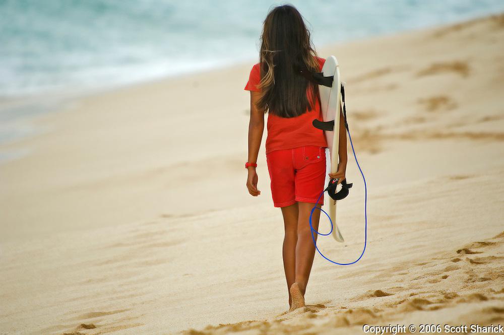 A girl dressed in red walks away with a surfboard n a Hawaiian Beach