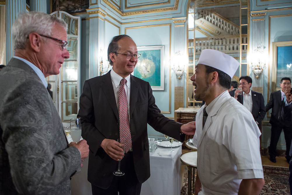 New York, NY - 3 June 2016. Chef David Bouley (left) inviting chef Kamiya (right), the personal chef of the Reiichiro Takahashi (center), the Japanese Ambassador, to visit him at brushstroke, Bouley's Japanese restaurant in New York. The invitation came at a reception following  a ceremony awarding Bouley the title Japanese Cuisine Goodwill Ambassador for his work in bringing Japanese cuisine to the U.S.
