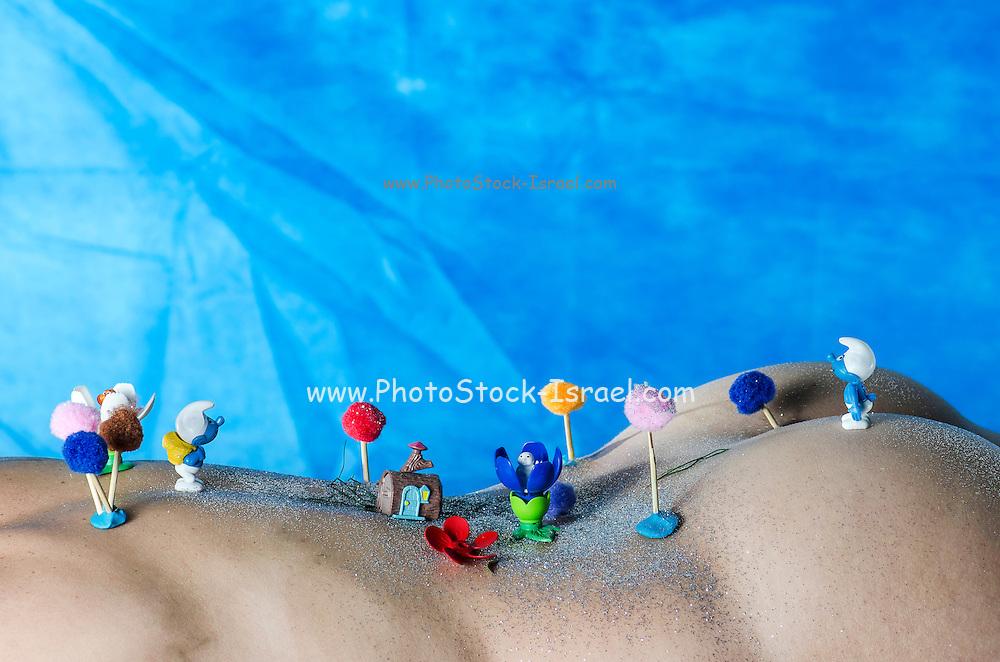 Miniature toy smerfs on a woman's torso
