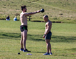 © Licensed to London News Pictures. 05/04/2020. London, UK. Two men do weight training in Richmond Park. Members of the public come out to exercise as temperatures reach 21c this weekend. Richmond Park seems quieter after the Government urged the public not to leave home during the fine weather as the Coronavirus crisis continues. Photo credit: Alex Lentati/LNP