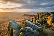 Higger Tor's shapely gritstone rocks make the foreground for this scene in the Peak District. Side-lit by the rising sun, they overlook the upper Burbage Valley and Hathersage Moor. Carl Wark, the site of an Iran Age hill fort can be seen in the middle distance. A winter landscape in England, UK.