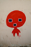 Alien Graffiti red figure with large head and square eyes and mouth