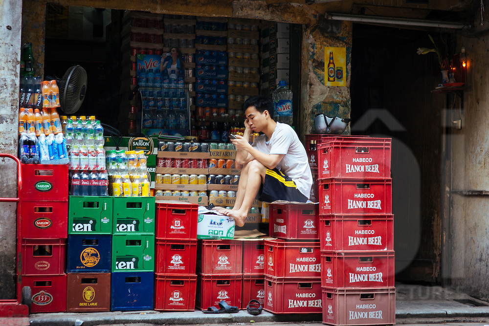 A young vendor sits on crates of beverages in a Hanoi shop, Vietnam Southeast Asia