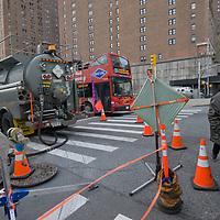 A man walks around a utility maintenance truck beside First Aveue in New York City.